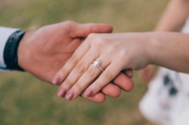A man and woman holding hands with the woman wearing a diamond engagement ring. (Photo: Transtudios Photography & Video/Pexels)