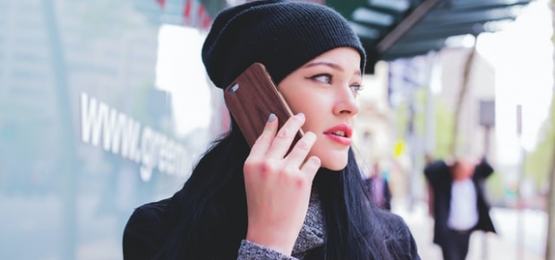 Woman wearing coat and winter cap talking on a cell phone. (Photo: Fezbot2000/Unsplash)