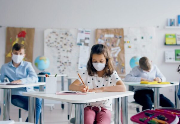 Students in a classroom sitting at desks studying while wearing masks. (Photo: Storyblocks)