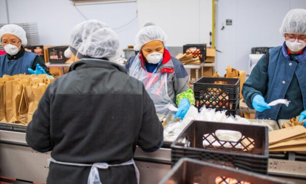 4 MCPS food service workers pack lunches for students. (Photo: Montgomery County Public Schools)