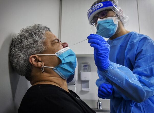 A gray haired woman gets a nasal swab in a doctor's office from a haeathcare worker wearing full protective gear. (Photo: Washington Post)