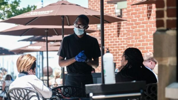 A waiter wearing a mask and gloves takes an order from two women outside at McCormick & Schmick's in National Harbor in June 2020. (Photo: Getty Images)
