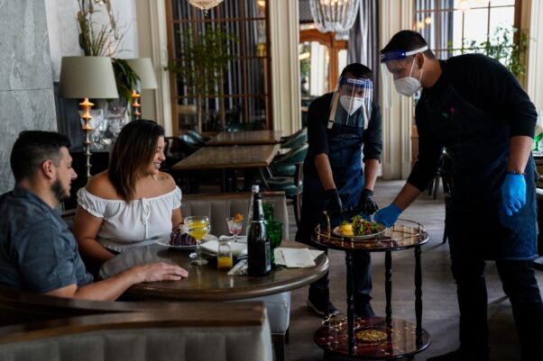 A man and woman are served food by two waiters wearing face shields, masks and gloves at a restaurant. (Photo: Kent Nishimura/Los Angeles Times)