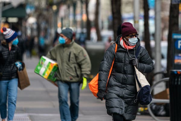 A man and woman woaking down a street dressed in winter coats, carrying packages and wearing masks. (Photo: Jeenah Moon/New York Times)