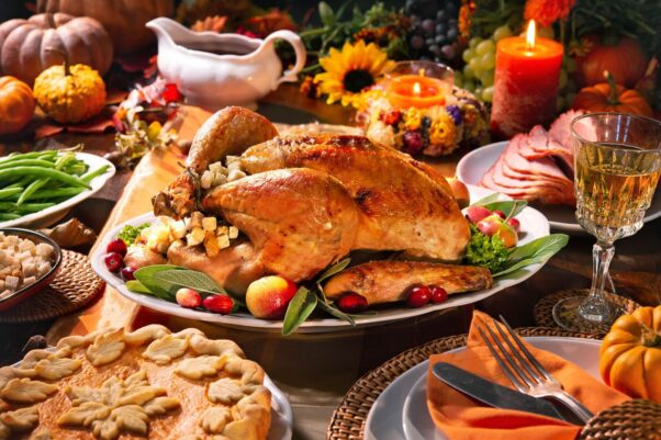 A Thanksgiving table with a turkey, ham, green beans, stuffying, gravy, a pie and decorations. (Photo: Shutterstock)