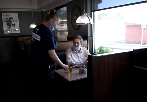 A waiter tends to diner inside a restaurant. Both are wearing masks. (Photo: Michael Loccisano/Getty Images)