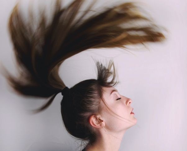 Worman with brown hair wearing a black shirt tosses her long ponytail back. (Photo: Eleanor/Unsplash)