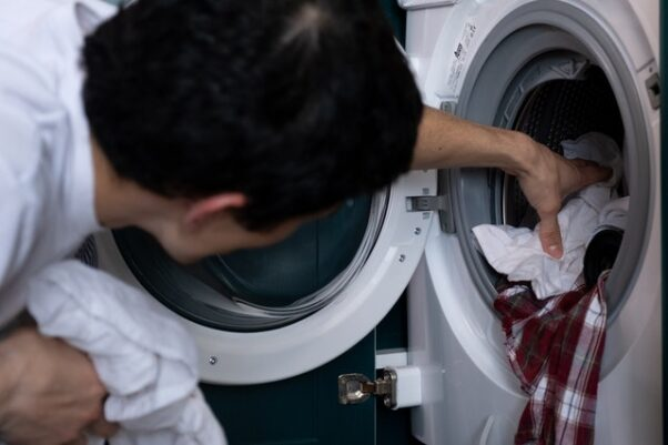 A man removing clothing from a white, front-end washer. (Photo: C Technical/Pexels)