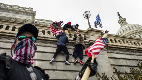 Donald Trump supporters scale the walls of the U.S. Capitol during an insurretion on Jan. 6, 2021. (Jason Andrew/New York TImes)