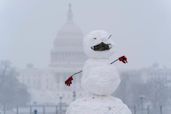 A snowman wearing a facial mask stands on the National Mall with the U.S. Capitol in the background. (Photo: Alex Brandon/AP)