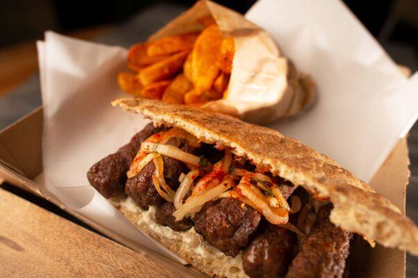 Ambar's Balkan kebab sandwich in a to-go box iwth a bag of fries. (Photo: Calypso Digital)