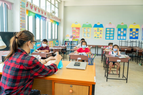 Group of school students with teacher sitting in classroom wearing masks and socially distanced. (Photo: Adobe Stock)