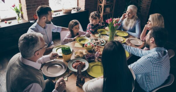 A family of adults and children sits around the dinner table enjoying Easter dinner. (Photo: Shutterstock)