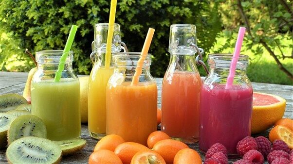 Five different juices in bottles surrounded by fruit. (Photo: Silviarita/Pixabay)
