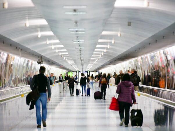 People with luggage walking through an airport. (Photo: Roman Mathon/Unsplash)