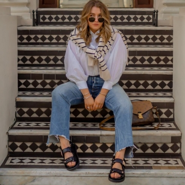 A woman sitting on outside steps in a white shirt, ripped jeans, Birkenstocks and sunglasses. (Photo: Elliee May)