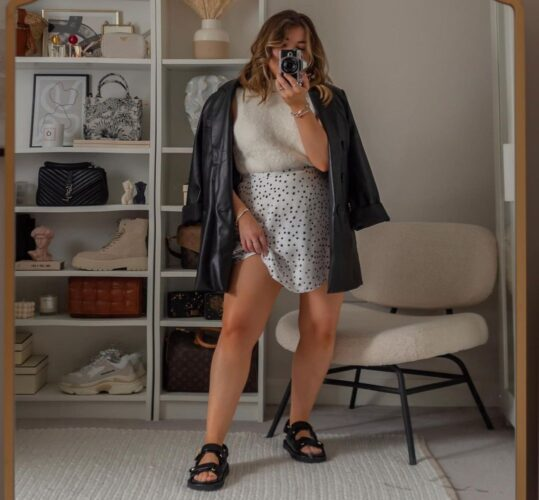 Woman inside taking a selfie wearing a white sweater, white skater skirt wiht black polka dots, a black leather jacket and Birkenstocks. (Photo: Elliee May)