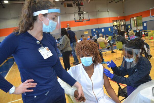 A Black woman get a COVID-19 shot from a Black nurse at the Benning-Stoddert Recreation Center on March 13, 2021, while a White nurse holds the patient's hand. (Photo: D.C. Housing Authority)