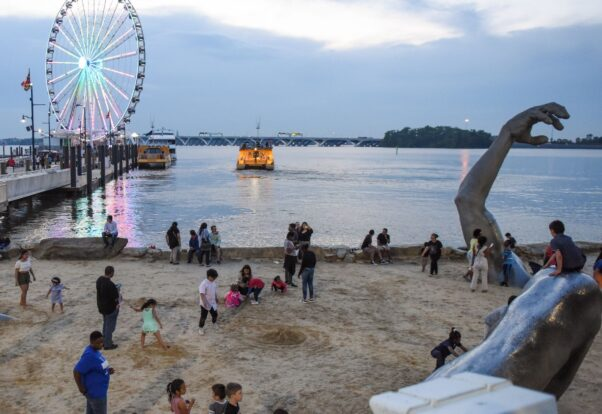 People without masks at the Awakening statue in National Harobor with the Capital Wheel in the background. (Photo: National Harbor)