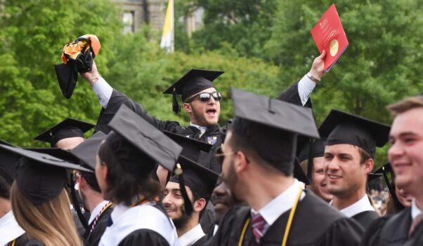 A graduate in sunglasses, cap and gown celebrates at Catholic University's 2019 commencement ceremony on campus. (Photo: Catholic University