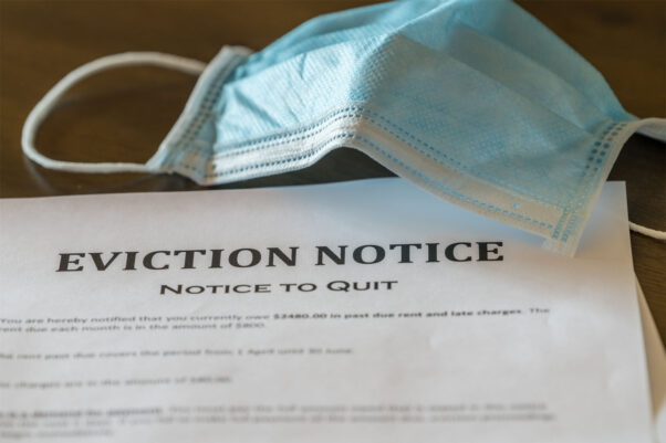 A facemask and eviction notice on wooden table. (Photo: Backyard Prodcutions/Getty Images)