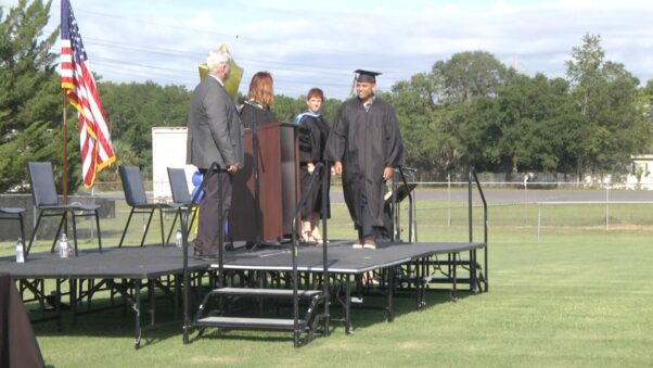 A student from Marion County Public Schools in Florida walks across an outdoor stage set up on a football field in his cap and gown on June 12, 2020. (Photo: WCJB)