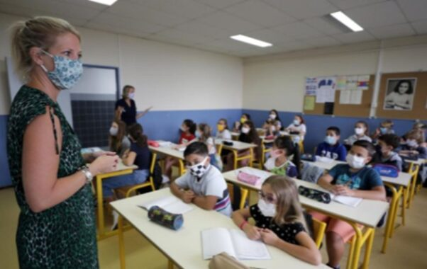 A masked teacher standing in front of a class of students wearing masks. (Photo: Reuters)