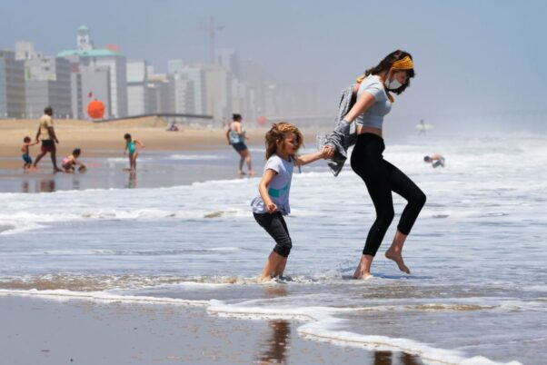 Victoria Faughnan, right, and Evelyn Faughnan play in the surf at Virginia Beach on May 22, 2020. (Photo: Steve Helber/AP)