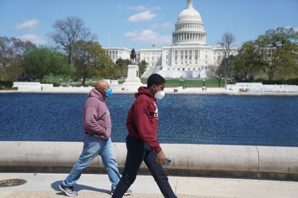Two Black men walk past the pool in front of the U.S. Capitol on April 11, 2021. (Photo: Liu Jie/Xinhua)