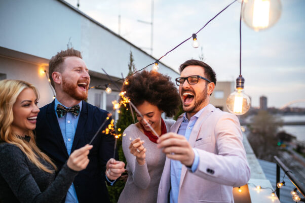 Four people at a formal outdoor party celebrating with sparklers. (Photo: iStock)