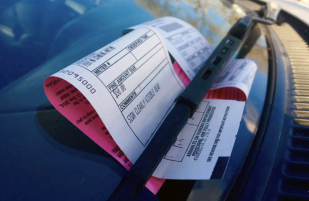 Close up of a car windshield with two D.C. parking tickets under the wiper. (Photo: D.C. Government)