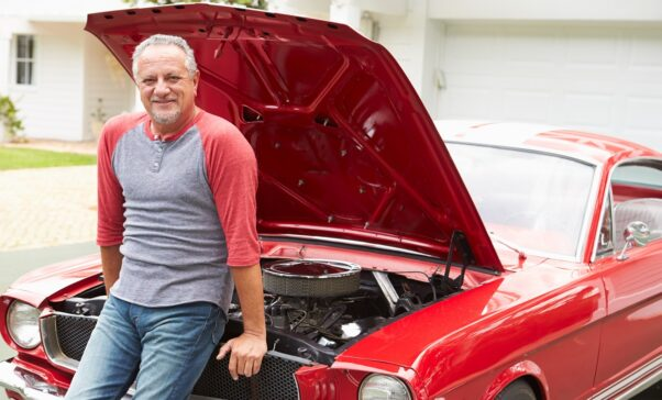 Retired senior man working on restored classic car smiling to camera. (Photo: monkeybusinessimages)
