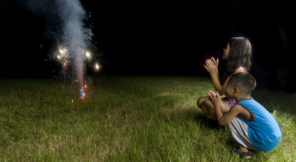 Two children squatting down watching sparks shoot into the sky from fireworks. (Photo: Two children squatting down watching sparks shoot into the sky from fireworks. (Photo: Shutterstock)Shutterstock)