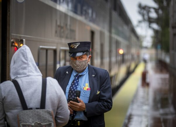 A conductor wearing a face mask takes a boarding passenger's ticket. (Photo: Los Angeles Times)