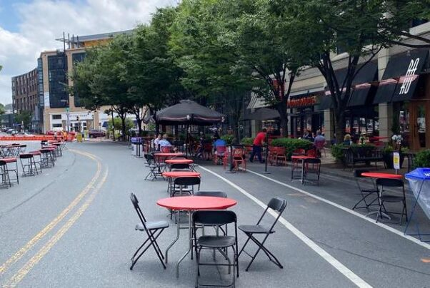 People eat at the Bethesda Streetery, a section of Woodmont Avenue that has been closed to vehicles and furnished with tables and chairs. (Photo: Montgomery County Department of Transportation)