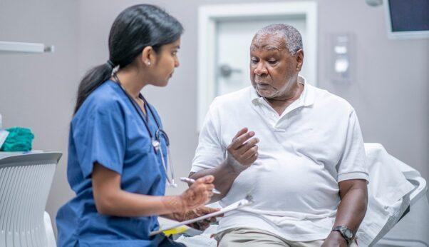 Black senior man talking to a female doctor in blue scrubs. (Photo; iStock)