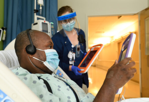 Nurse Shelby Cahill helps Shawn Hoke, a patient in the Progressive Cardiac Care Unit, navigate the MyChart Bedside tablet, which is equipped with apps to help patients stay connected to the outside world during their hospital stay. (Photo: Johns Hopkins Medicine)