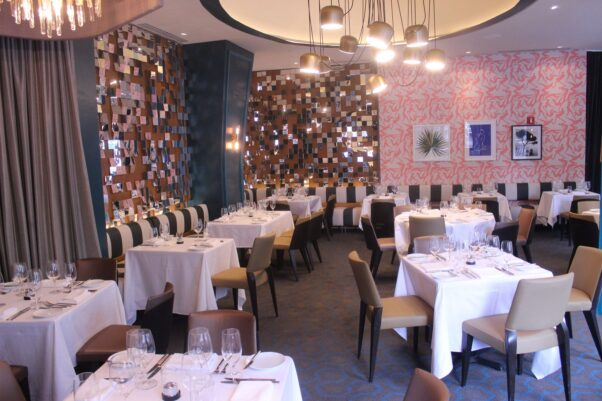 The main dining room with mirror tiles, coral wallpaper and black and white stiped banquettes. (Photo: Mark Heckathorn/DC on Heels)