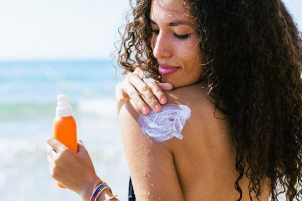 A Black woman at the beach applying sunscreen to her left shoulder. (Photo: BonninStudio/Stocksy)