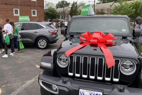 People look at two cars, decorated with red bows and Win Me signgs, D.C. is giving away for getting a COVID-19 vaccination east of the Anacostia River. (Photo: John Domen/WTOP)