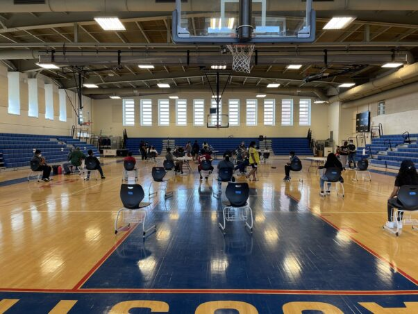 People waiting in the gym and Anacostia High School to get a COVID-19 vaccination. (Photo: Ricky A. Brown/Twitter)