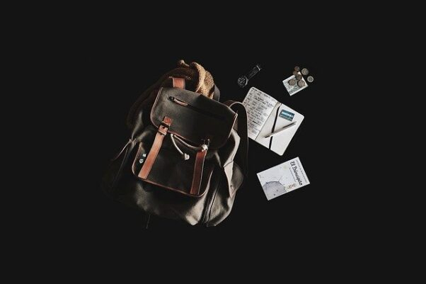A backpack with a watch, some coins and a passport on a black background. (Photo: Pexels)