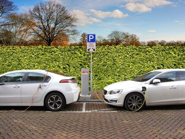 Two white electric cars parked at a public charging station. (Photo: joenomias/Pixabay)