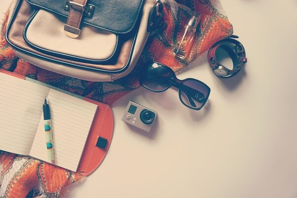 A travel bag with a watch, sunglasses and Go Pro on a white background. (Photo: freephotocc/Pixabay)