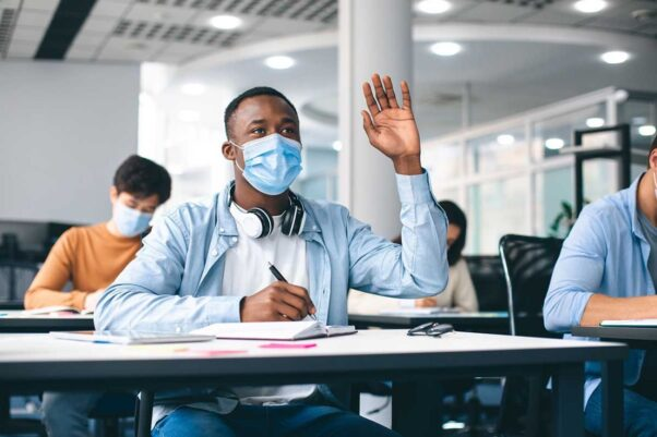 A Black teen sitting at his desk holding up his hand while wearing a face mask. (Photo: Shutterstock)
